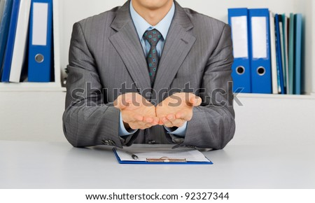 Businessman in elegant suits asking for money, man in blue suit lending a helping hand, sitting at the desk at office