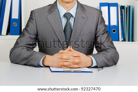 Businessman in elegant suits working with documents sitting at the desk at office