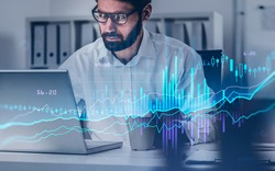 Businessman in eyeglasses analysing stock market changes, sitting in front of the laptop, double exposure. Concept of trading, blue and violet lines and candlesticks