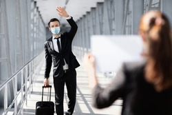 Businessman in face mask waving to assistance with placard, meeting in airport. Middle-aged entrepreneur with suitcase arrived for business meeting, greeting business partner or representative