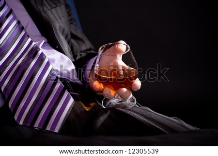 Businessman in formal dress relax with glass of cognac over black background. Focus on hand with glass.