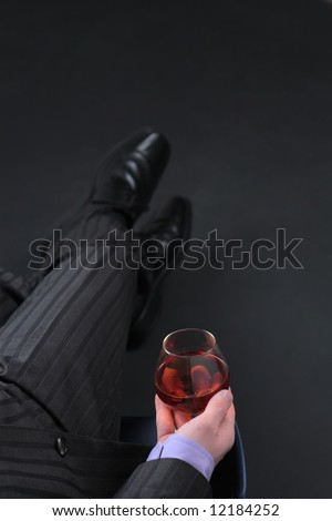 Businessman in formal dress relax with glass of cognac over black background. Image with copyspace. Focus on glass.