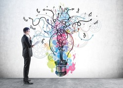 Businessman in formal suit is looking at colourful pink, blue and yellow sketch with light bulb, arrows, lines and cogwheels on concrete wall. Concept of imagination and inspiration for creative ideas