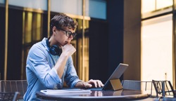 Businessman in formal wear watching online webinar during distance work with startup project on portable pc connected to 4g wireless, male trader in spectacles checking information on website