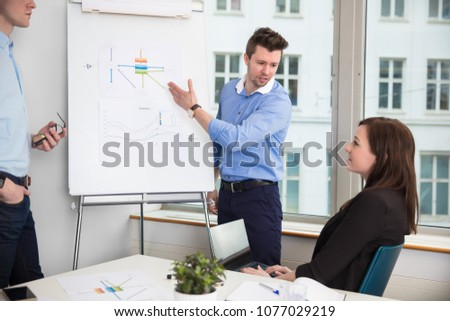 Businessman In Formals Giving Presentation To Colleagues #1077029219