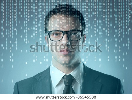 Businessman in front of a computer screen with binary code on it