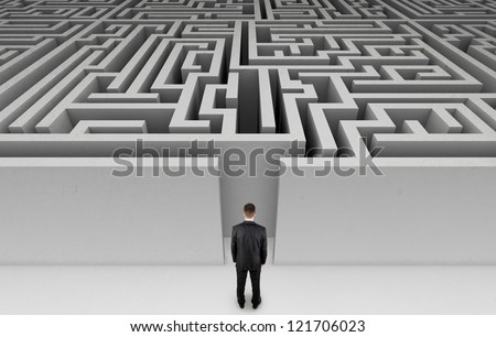Businessman in front of a huge maze - stock photo