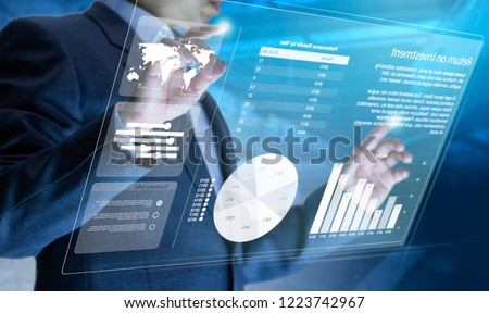 Businessman in front of virtual modern computer touch screen analysing on investment risk managment and return on investment analysis #1223742967