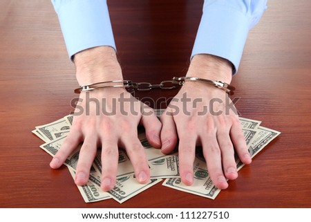 Businessman in handcuffs counts the money for bribes