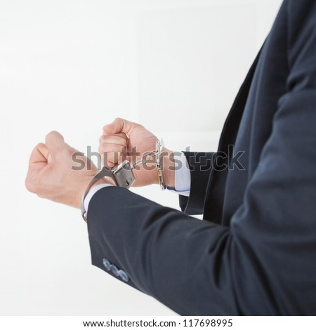 Businessman in handcuffs getting arrested for white collar crimes