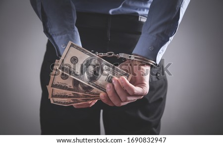 Businessman in handcuffs holding dollar banknotes. Corruption Foto stock ©