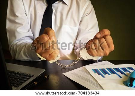 Businessman in handcuffs. White collar crime concept. #704183434