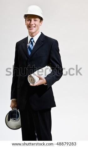 Businessman in hard-hat holding blueprints