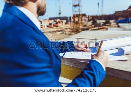 Businessman in hardhat and suit making notes on plans at construction site