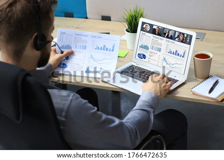 Businessman in headphones talking to her colleagues in video conference. Multiethnic business team working from home using laptop, discussing financial report of their company.