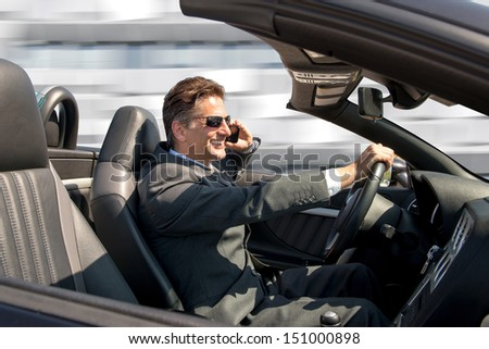 Businessman in his convertible car with cellphone