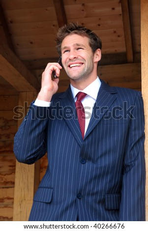 Businessman in his late twenties standing at a rural bus stop talking on his mobile phone