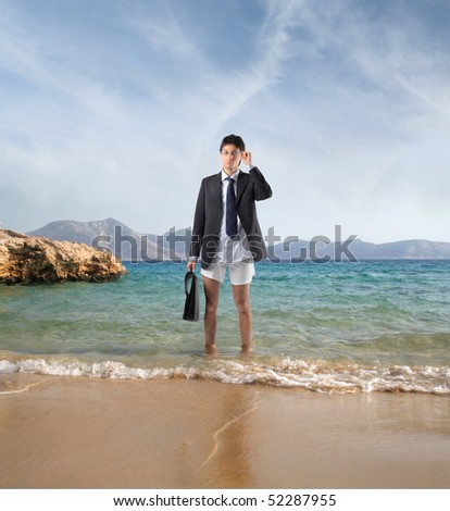 Businessman in jacket and boxers standing on the sand of a beach
