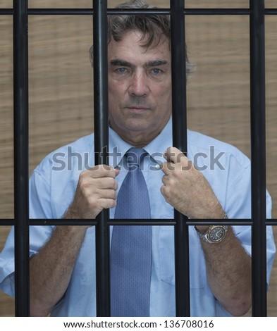 businessman in jail behind bars