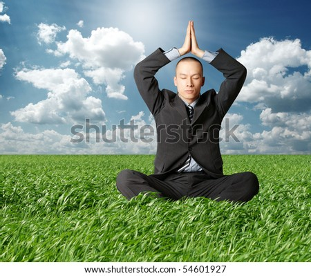 businessman in lotus pose in green grass on blue summer sky