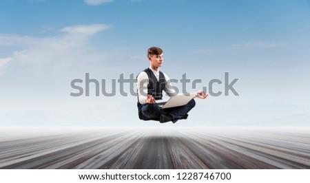 Businessman in lotus pose. Mixed media #1228746700