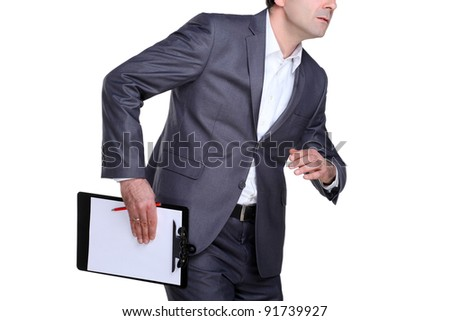 Businessman in motion holding his files and pencile in one hand