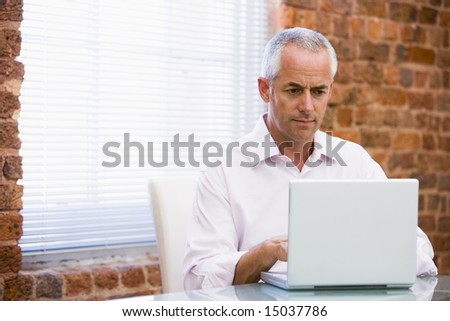 Businessman in office looking at laptop