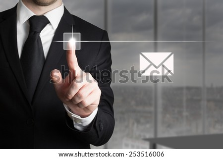 businessman in office pushing touchscreen button mail symbol