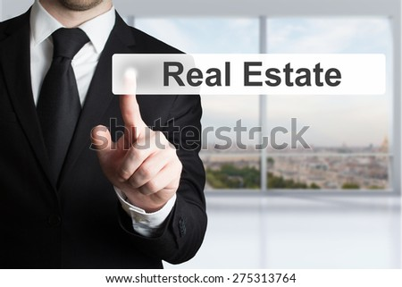 businessman in office room pushing button real estate