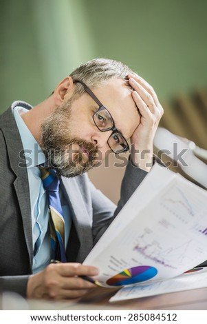 businessman in office thinks holding head hand. in the office