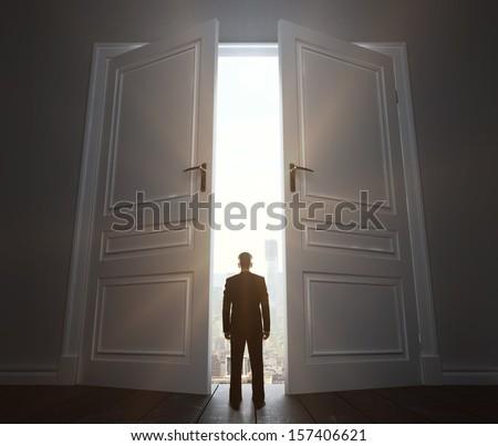 businessman in room with big door to city