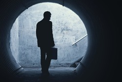 Businessman in Silhouette Walking in a dark tunnel. With room for your Text