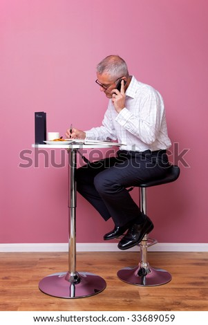 Businessman in smart casual attire sat on a bar stool in a cafe working through his lunch break.