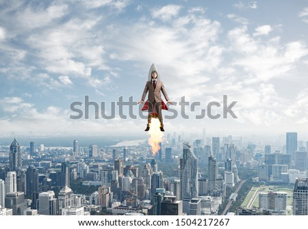 Businessman in suit and aviator hat flying on rocket. Superhero businessman flying with jetpack rocket in blue sky above modern downtown. Successful business startup. Career growth concept.