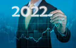 Businessman in suit forecast analysis plan profit chart. economic forecasts for 2022. businessman writes 2022 on virtual screen. economic recovery after fall due to covid 19 coronavirus pandemic