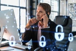 Businessman in suit has conference call of cyber security in compliance division to protect clients confidential information. IT hologram lock icons over office background with panoramic windows.