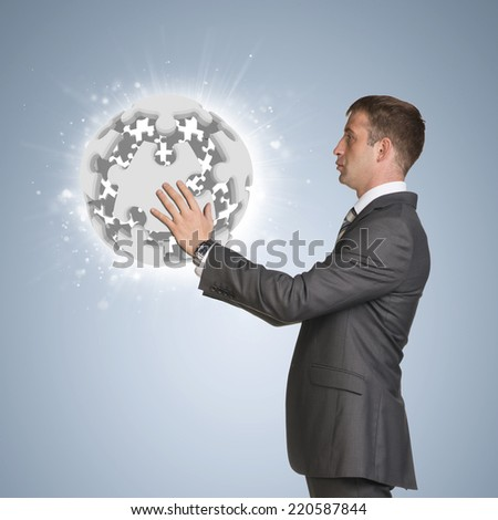 Businessman in suit hold jigsaw puzzle sphere. Blue background