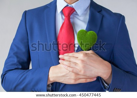 Businessman in suit holding a green heart shape - white background - indicates ecofriendly , social and environmental responsiblility business concept