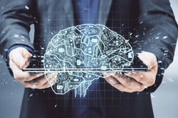 Businessman in suit holding tablet with glowing circuit brain hologram. AI and business communication concept.
