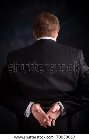 Businessman in suit is handcuffed behind his back.