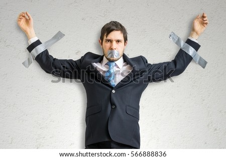 Businessman in suit is taped to the wall with adhesive tape. #566888836