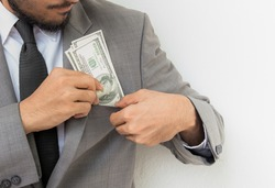 Businessman in suit puts a bunch of American Dollars into jacket pocket. Isolated on white background.