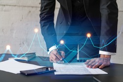 Businessman in suit signs contract. Double exposure with financial chart hologram. Man signing mortgage agreement. Real estate market analysis and investment concept.