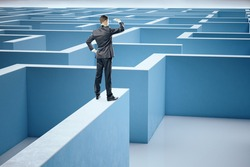 Businessman in suit standing on middle of a blue labyrinth. Business and challenge concept.