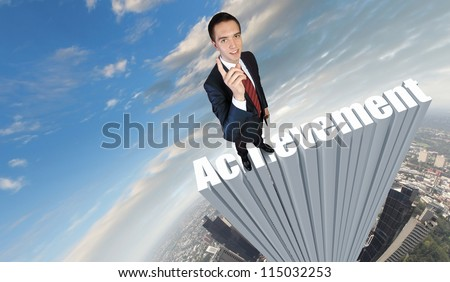 Businessman in suit standing on the word Achievement