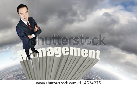 Businessman in suit standing on the word Management