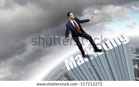 Businessman in suit standing on the word Marketing