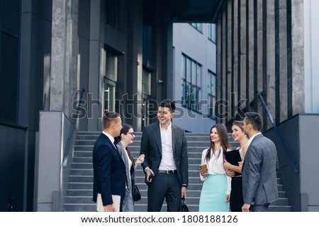 Businessman in suit talking to business people colleagues or partner. Male leader discussing work at team meeting or group negotiations having conversation Сток-фото ©