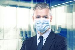 Businessman in suit wearing a face mask as protection against the Covid-19 or coronavirus standing with folded arms over a office background