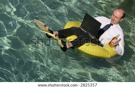 Businessman in suit with laptop on his lap in a sailing dingy, wearing flippers with the crystal clear ocean around him